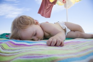 one year baby with white diaper sleeping on striped colored beach towel under parasol