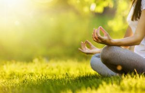 woman in yoga pose in park with sunshine